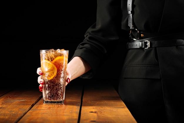 Młoda kobieta trzyma szklankę świeżego koktajlu mrożonej herbaty long island