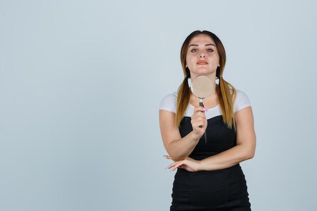 Młoda kobieta trzyma szkło powiększające