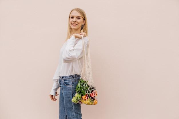 Młoda kobieta trzyma sznur torba na zakupy z owocami. torba ekologiczna wielokrotnego użytku na zakupy