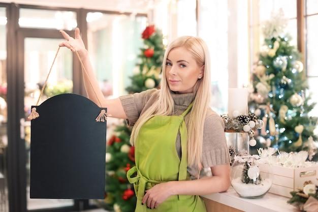 Młoda kobieta trzyma szyld w kwiaciarni. właściciel małej firmy