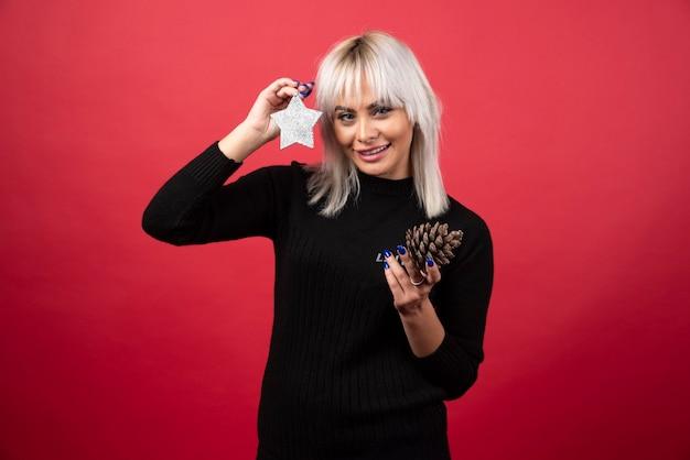 Młoda kobieta trzyma szyszkę z gwiazdą na czerwonej ścianie.