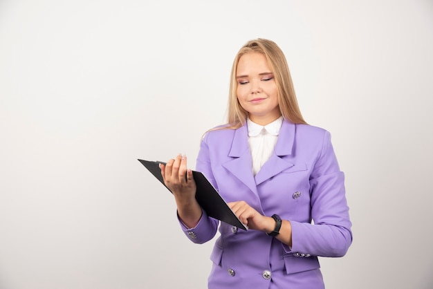 Młoda kobieta trzyma tabletkę na białym.
