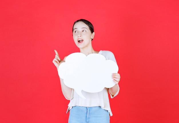 Młoda kobieta trzyma tablicę pomysłów i wskazuje palcem w górę