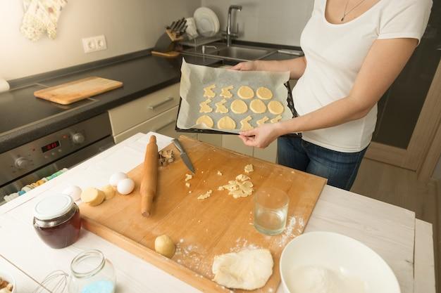 Młoda kobieta trzyma tacę z ciastkami i wkłada ją do piekarnika