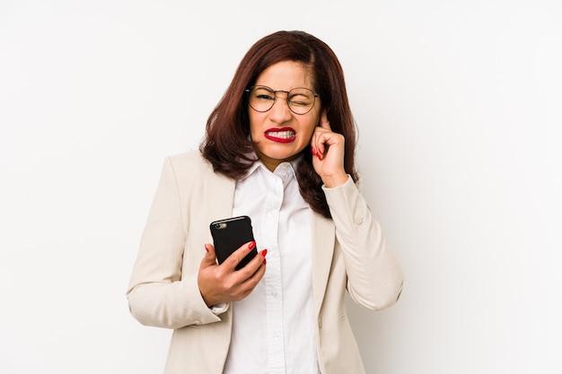 Młoda kobieta trzyma telefon komórkowego odizolowywał nakrywkowych ucho z rękami