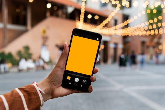 Młoda kobieta trzyma telefon komórkowy, aby zrobić zdjęcie w mieście.