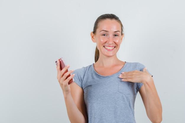 Młoda kobieta trzyma telefon komórkowy, pokazując się w szarym t-shircie i patrząc radośnie. przedni widok.