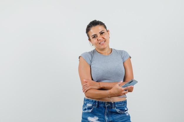 Młoda kobieta trzyma telefon komórkowy w koszulce, spodenkach i wesoło patrząc.