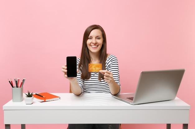 Młoda kobieta trzyma telefon komórkowy z pustym pustym ekranem i kartą kredytową siedzieć przy białym biurku z współczesnym laptopem pc na białym tle na pastelowym różowym tle. osiągnięcie kariery biznesowej. skopiuj miejsce.