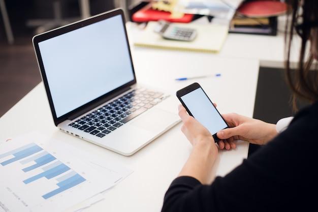 Młoda kobieta trzyma telefon. miejsce pracy w pobliżu okna z laptopem. ścieśniać