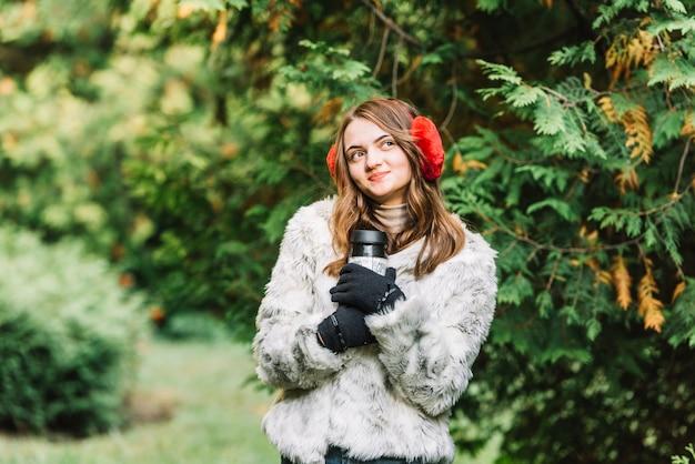 Młoda kobieta trzyma termosy w iglastym parku w nausznikach