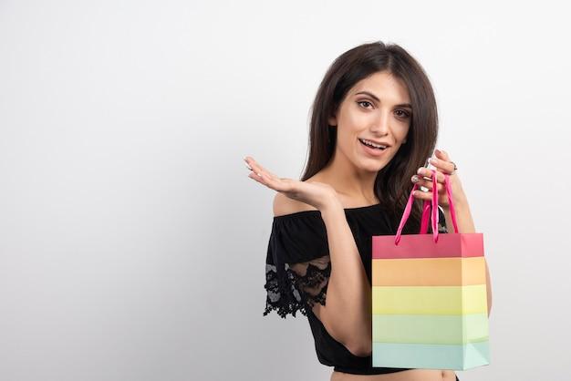 Młoda kobieta trzyma torbę na prezent.
