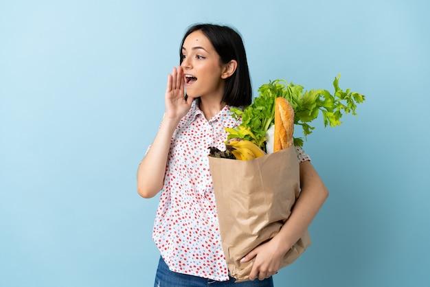 Młoda kobieta trzyma torbę na zakupy spożywcze, krzycząc z szeroko otwartymi ustami na bok
