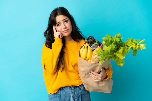 Młoda kobieta trzyma torbę na zakupy spożywcze na białym tle na niebieskiej ścianie myśli pomysł