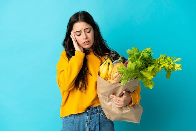 Młoda kobieta trzyma torbę na zakupy spożywcze na białym tle na niebiesko z bólem głowy