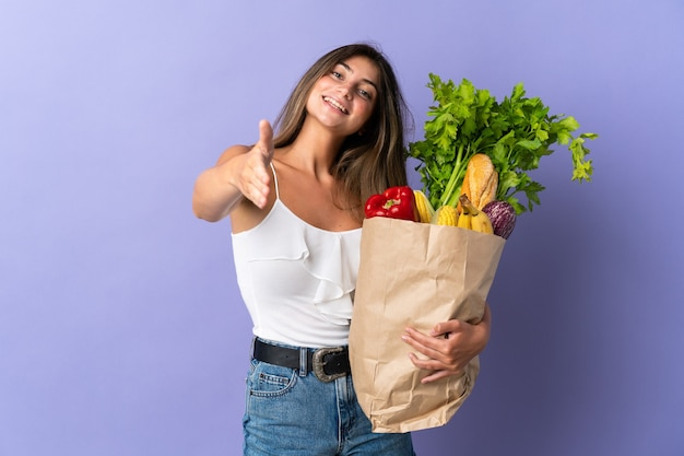 Młoda kobieta trzyma torbę na zakupy spożywcze, ściskając ręce za zamknięcie dobrej oferty