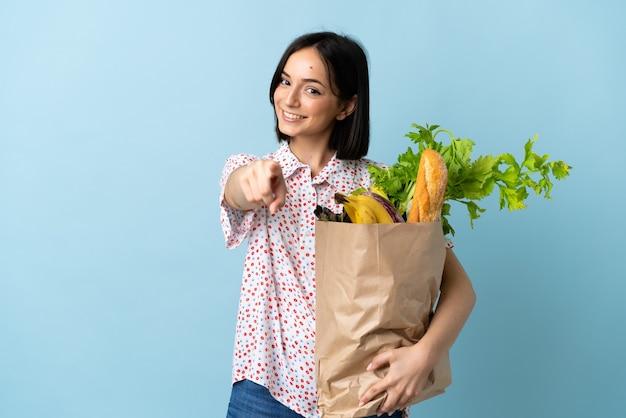 Młoda kobieta trzyma torbę na zakupy, wskazując przód z happy wypowiedzi