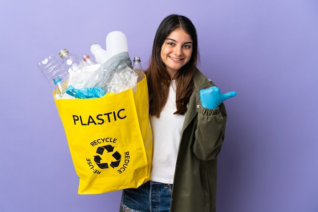 Młoda kobieta trzyma torbę pełną plastikowych butelek do recyklingu fioletowy, wskazując na bok, aby przedstawić produkt