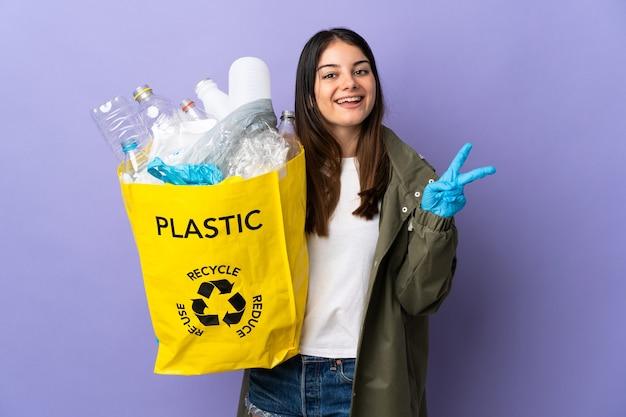 Młoda kobieta trzyma torbę pełną plastikowych butelek do recyklingu na białym tle na fioletowej ścianie, uśmiechając się i pokazując znak zwycięstwa