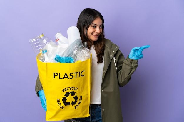 Młoda kobieta trzyma torbę pełną plastikowych butelek do recyklingu na białym tle na fioletowej ścianie, wskazując palcem w bok i prezentuje produkt