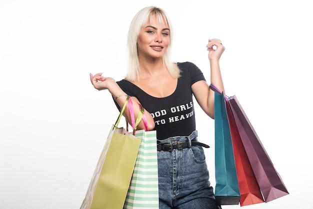 Młoda kobieta trzyma torby na zakupy na białej ścianie z happy wypowiedzi.