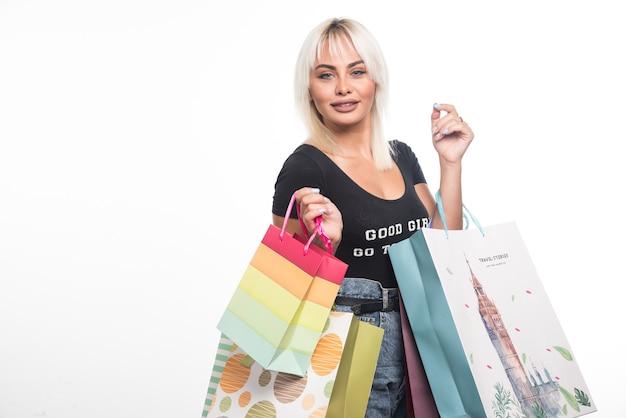 Młoda kobieta trzyma torby na zakupy na białej ścianie.