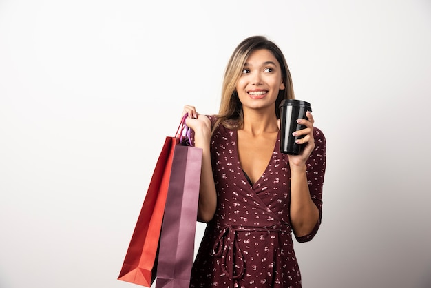 Młoda kobieta trzyma torby sklepowe i kubek napoju na białej ścianie.