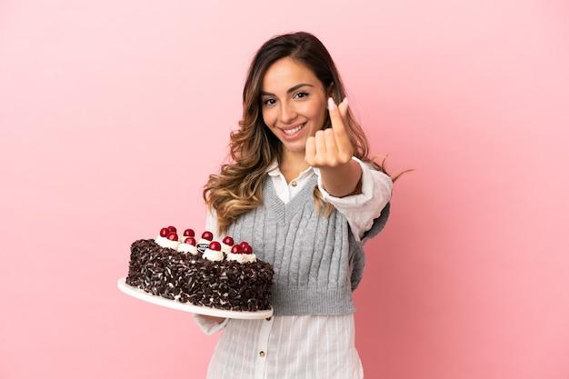 Młoda kobieta trzyma tort urodzinowy na odosobnionym różowym tle robienia pieniędzy gest
