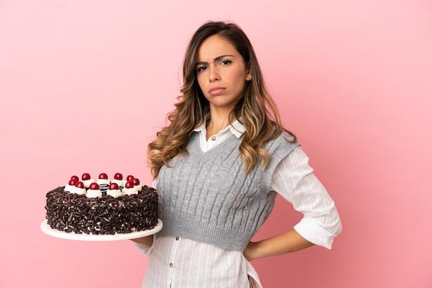 Młoda kobieta trzyma tort urodzinowy na odosobnionym różowym tle