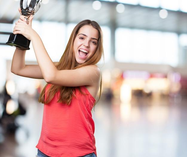 Młoda kobieta trzyma trofeum na białym tle