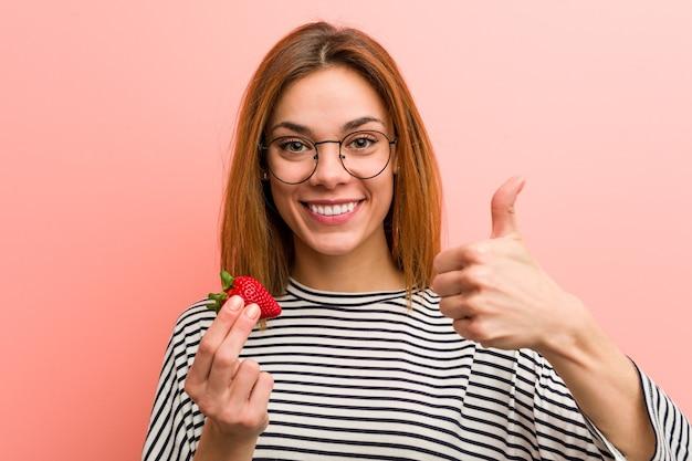 Młoda kobieta trzyma truskawkę uśmiechając się i podnosząc kciuk do góry