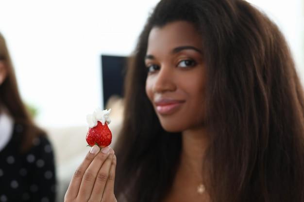 Młoda kobieta trzyma truskawkę ze śmietaną