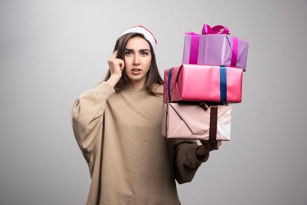 Młoda kobieta trzyma trzy pudełka prezentów świątecznych.