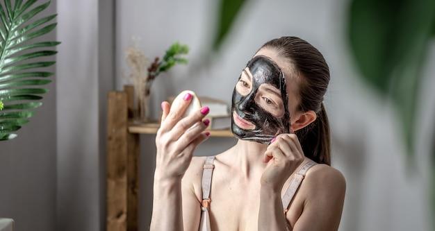 Młoda kobieta trzyma w dłoni lusterko i zdejmuje z twarzy kosmetyczną czarną maskę