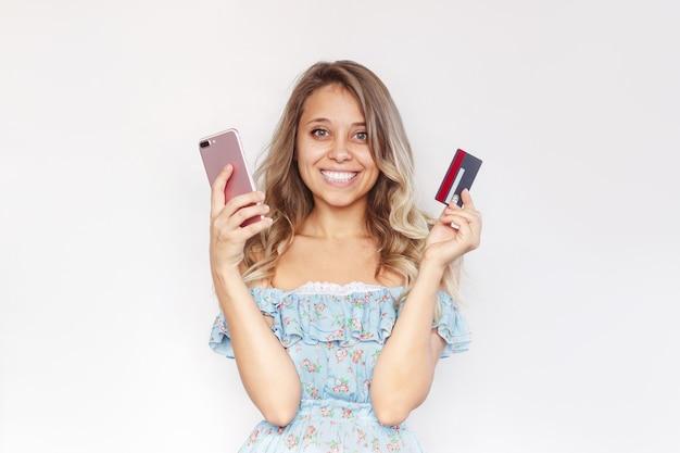 Młoda kobieta trzyma w dłoni plastikową kartę kredytową i telefon komórkowy, aby zapłacić za zakupy online