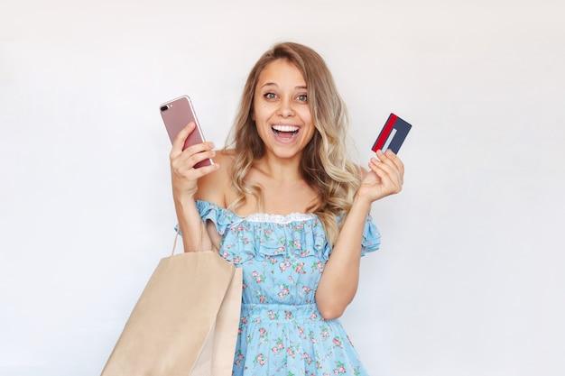 Młoda kobieta trzyma w dłoni telefon komórkowy z kartą kredytową i papierową torbę, aby zapłacić za zakupy