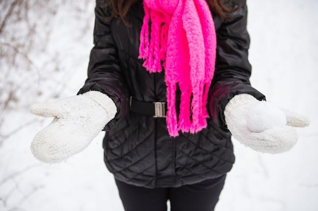 Młoda kobieta trzyma w rękach naturalny miękki biały śnieg, aby zrobić śnieżkę, uśmiechając się w zimny zimowy dzień w lesie, na zewnątrz.