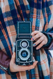 Młoda kobieta trzyma w rękach stary aparat vintage. fotograf dziewczyna.