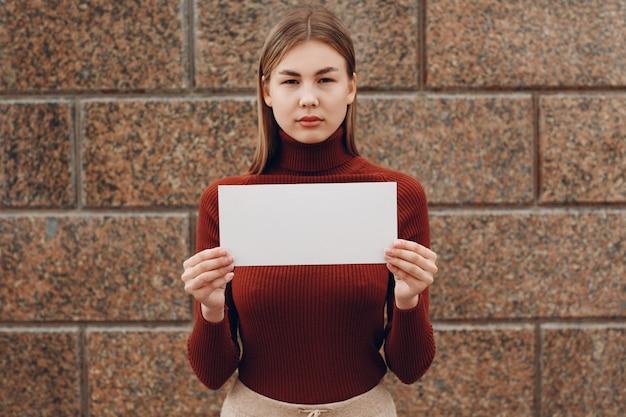 Młoda kobieta trzyma w ręku plakat z białej księgi. dziewczyna z białym pustym arkuszem szablonu w rękach.