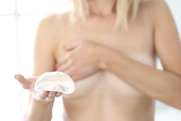 Młoda kobieta trzyma w ręku silikonowy implant piersi