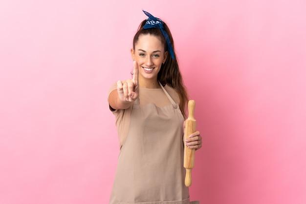 Młoda kobieta trzyma wałek do ciasta pokazując i podnosząc palec