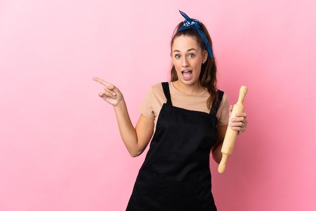 Młoda kobieta trzyma wałek do ciasta zaskoczony i wskazując palcem na bok