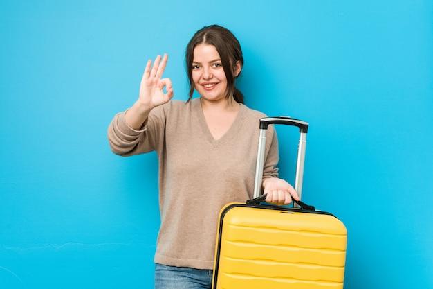 Młoda kobieta trzyma walizkę rozochoconą i ufną pokazuje ok gest.