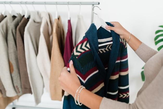 Młoda kobieta trzyma wieszak z nowym ciepłym swetrem z dzianiny, wybierając ubrania z sezonowej kolekcji