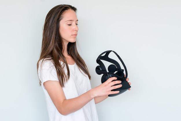 Młoda kobieta trzyma wirtualnej rzeczywistości gogle słuchawki, pole vr. połączenie, technologia, nowa generacja, koncepcja postępu. studio strzał w kolorze szarym.