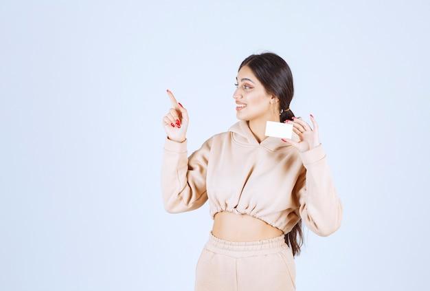 Młoda kobieta trzyma wizytówkę i wskazuje na kogoś