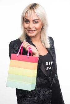 Młoda kobieta trzyma worek kolorowy prezent na białym tle. wysokiej jakości zdjęcie