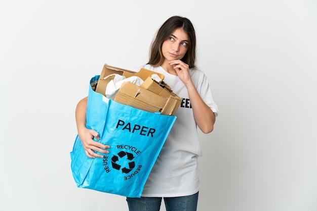 Młoda kobieta trzyma worek recyklingu pełnego papieru do recyklingu na białym tle i patrząc w górę