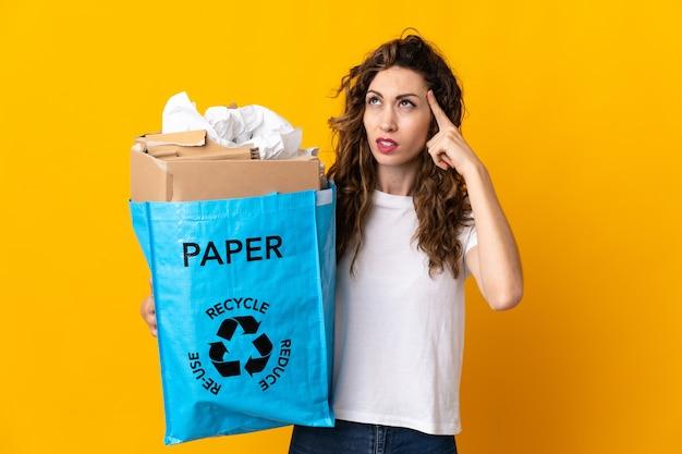 Młoda kobieta trzyma worek recyklingu pełnego papieru do recyklingu