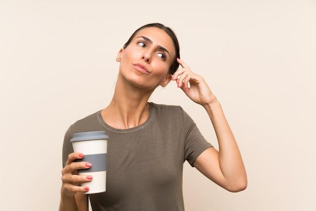 Młoda kobieta trzyma wynos kawę ma wątpliwości i wprawiać w zakłopotanie wyraz twarzy